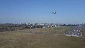 Colpo aereo di piccolo aeroplano dell'elica che decolla dalla pista dell'aeroporto della città un giorno soleggiato Immagini Stock Libere da Diritti