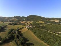 Colpo aereo di piccolo villaggio circondato di natura di Monti Sibillini National Park, Collevecchio, Macerata, Italia Fotografie Stock