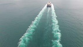 Colpo aereo di stupore 4k di una nave porta-container del carico che salpa nelle onde di oceano un giorno nuvoloso video d archivio