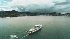 Colpo aereo di una barca di giro con l'ondeggiamento della bandiera svizzera che si muove sul lago Lucerna, Svizzera stock footage