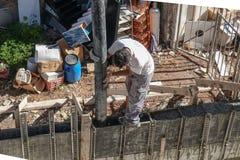 Colpo aereo di una condizione dell'uomo sopra shuttering e la guida del cemento di versamento dello scivolo del cemento nello shu fotografie stock