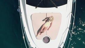 Colpo aereo di una giovane donna che si rilassa e che prende il sole su un yacht - barca che è parcheggiata al marinaio stock footage