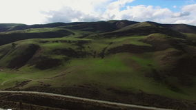 Colpo aereo di una strada principale ed i grandi campi e colline verdi stock footage