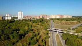 Colpo aereo sopra la città con la vista su una piccola strada, l'area karting con le automobili commoventi e le alte costruzioni video d archivio