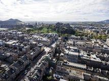 Colpo aereo storico 3 di giorno soleggiato della Castle Rock della città di Edimburgo immagine stock libera da diritti