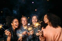 Colpo all'aperto degli amici di risata con le stelle filante Immagini Stock