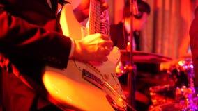 Colpo alto vicino degli uomini che giocano chitarra elettrica in scena alla notte stock footage