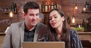Colpo alto vicino dei soci commerciali maschii e femminili che discutono sopra che cosa è sullo schermo del computer portatile archivi video