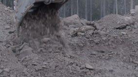 Colpo alto vicino del movimento lento del suolo di scavatura dell'escavatore con ghiaia e le pietre stock footage
