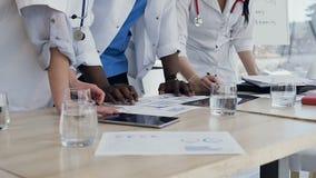 Colpo alto vicino delle mani di tre medici durante la discussione del risultato di analisi del sangue archivi video