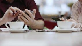 Colpo alto vicino delle mani maschii e femminili facendo uso dei loro smartphones dalla tavola in un ristorante stock footage