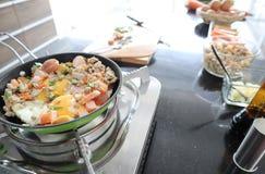 Colpo alto vicino delle uova della pentola fritta con carne di maiale e la salsiccia tritate sullo storve fotografia stock