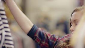 Colpo alto vicino di giovane bella donna allegra che esamina camicia che ha trovato su uno scaffale in un negozio di vestiti stock footage