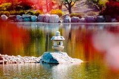 Colpo alto vicino di una statua della lanterna giapponese in mezzo ad uno stagno incorniciato dalle foglie rosse fotografia stock