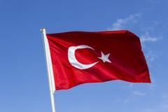 Colpo anteriore di prospettiva della bandiera d'ondeggiamento variopinta del turco con il fondo blu del cielo aperto a Smirne in  fotografia stock