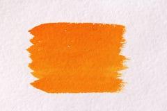 Colpo arancio con una spazzola fatta degli acquerelli Priorità bassa di carta fotografie stock libere da diritti