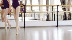 Colpo basso delle gambe del ` delle ragazze in scarpe di balletto che camminano sulle punte dei piedi che fanno i punti sul pavim stock footage