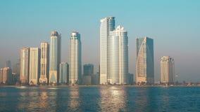 Colpo bloccato della città Grande città a lungomare Increspi l'onda sull'acqua, sul cielo blu e sui grattacieli alti Concetto di  stock footage