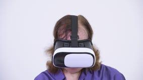 Colpo capo dell'uomo senior felice che per mezzo della cuffia avricolare di realtà virtuale archivi video