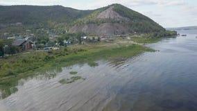 Colpo commovente aereo sopra il fiume, la riva ed il villaggio nel giorno di estate video d archivio
