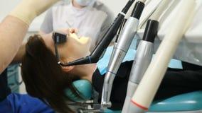 Colpo degli strumenti del dentista sul primo paziente della sfuocatura e di piano che si siede sulla sedia del dentista sui prece stock footage