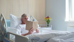 Colpo del carrello di un libro di lettura invecchiato premuroso dell'uomo in un ospedale video d archivio