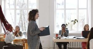 Colpo del carrello, giovane donna sorridente felice di affari che cammina lungo l'ufficio moderno incoraggiato ed accolto favorev video d archivio