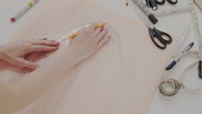 Colpo del dettaglio o primo piano della cucitrice mentre lei che lavora con la curva o il modello di misura Le mani della donna a archivi video