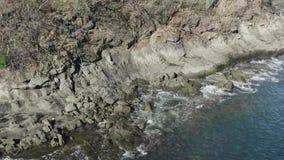 Colpo del fuco che tir indietroare dal litorale roccioso come spruzzata dell'onda stock footage