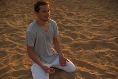 Colpo del giovane in buona salute che sta nella posa di yoga sulla sabbia Fotografia Stock