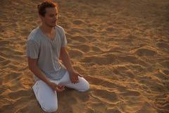 Colpo del giovane in buona salute che sta nella posa di yoga sulla sabbia Fotografia Stock Libera da Diritti