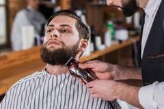 colpo del primo piano del barbiere che rade uomo immagini stock