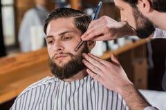 colpo del primo piano del barbiere che rade uomo immagine stock