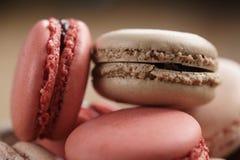 Colpo del primo piano dei macarons colorati pastello con sapore rosa e del caramello della fragola, in ciotola di legno Fotografie Stock