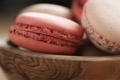 Colpo del primo piano dei macarons colorati pastello con sapore rosa e del caramello della fragola, in ciotola di legno Fotografie Stock Libere da Diritti