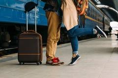 Colpo del primo piano dei piedi della donna che stanno sulla punta dei piedi mentre abbracciando il suo uomo al binario ferroviar Fotografie Stock Libere da Diritti