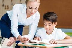 colpo del primo piano dell'insegnante che aiuta scolaro felice immagine stock