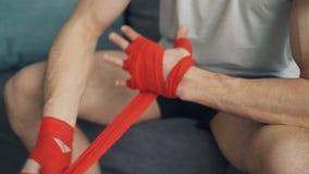 Colpo del primo piano dell'uomo che avvolge le mani con le fasciature protettive del polso che applaudono le mani archivi video