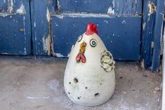 Colpo del primo piano della figura fatta a mano del gallo vicino alla porta di legno blu immagini stock libere da diritti