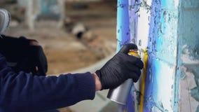 Colpo del primo piano della mano maschio in pittura dell'aerosol della tenuta del guanto protettivo e dei graffiti della pittura  stock footage