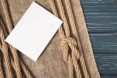 colpo del primo piano di Libro Bianco in bianco su tela di sacco e sulle corde annodate nautiche marroni immagini stock libere da diritti