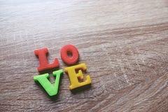 """colpo del primo piano di parola """"di amore """"con un fuoco selettivo delle lettere magnetiche variopinte per il San Valentino immagini stock"""