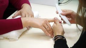Colpo del primo piano di una donna in un salone dell'unghia che riceve un manicure da un estetista con l'archivio di unghia Donna archivi video