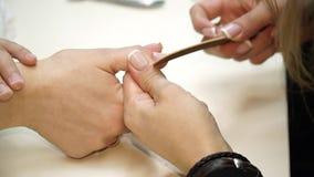 Colpo del primo piano di una donna in un salone dell'unghia che riceve un manicure da un estetista con l'archivio di unghia Donna stock footage