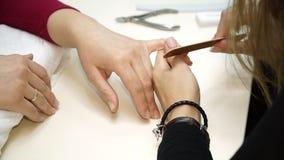 Colpo del primo piano di una donna in un salone dell'unghia che riceve un manicure da un estetista con l'archivio di unghia Donna video d archivio