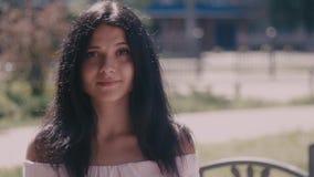 Colpo del ritratto di bella giovane donna castana esaminando la macchina fotografica su fondo vago nella via della città Fine in  archivi video