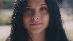 Colpo del ritratto di bella giovane donna castana esaminando la macchina fotografica su fondo vago nella via della città Fine in  video d archivio