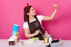 Colpo dell'interno della giovane signora carismatica smilling stante che fa selfie alla cucina mentre cucinando nuovo piatto deli fotografia stock libera da diritti