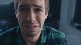 Colpo dell'uomo triste che grida con gli strappi a casa Concetto di dramma Flussi dello strappo giù la sua guancia stock footage
