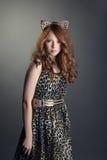 Colpo della bambina in orecchie del vestito e di gatto dalla stampa del leopardo Fotografie Stock Libere da Diritti